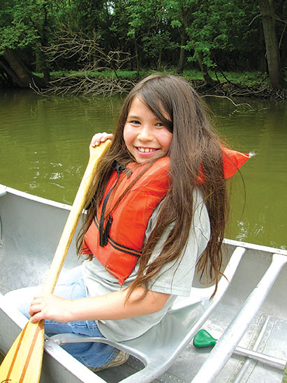 child canoeing at summer camp