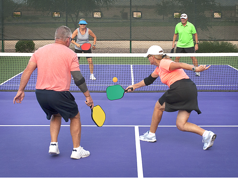 adults playing outdoor pickleball